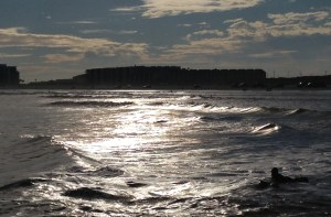 The sun broke free from the clouds and cast a silvery shimmer on the surf.